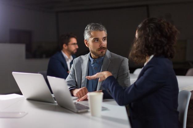 Коллеги обсуждают работу в темном офисе