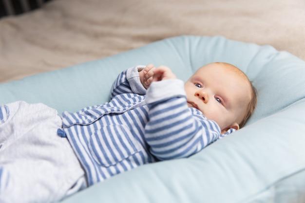 青とグレーの服で好奇心が強い物思いに沈んだ赤髪の赤ちゃん
