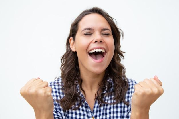 Взволнованная молодая женщина поднимает кулаки