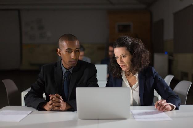 Целенаправленные деловые партнеры, глядя на ноутбук в офисе