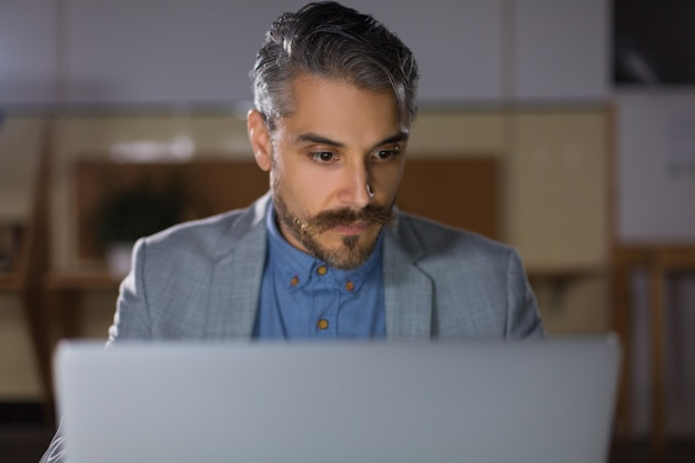 Вид спереди сосредоточенного человека, смотрящего на ноутбук