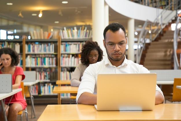 ノートパソコンで入力する焦点を当てた男の正面図