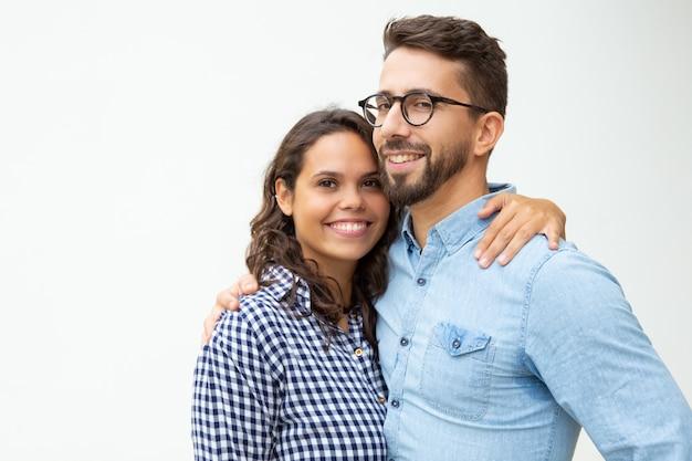 幸せな若いカップルに立っていると抱きしめる