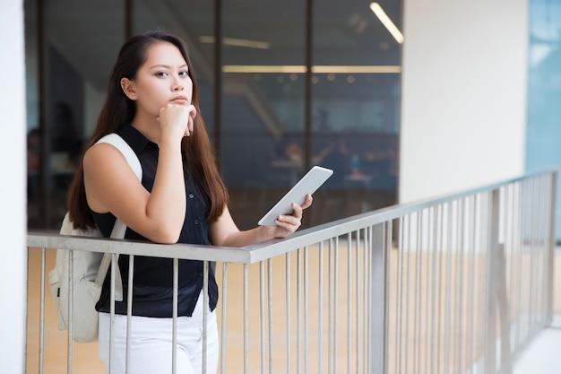 Задумчивая молодая женщина с планшетным пк смотрит в камеру