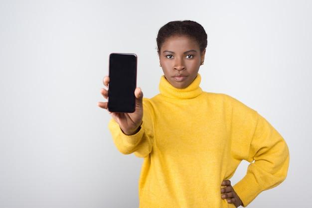 空白の画面を持つ携帯電話を示すアフリカ系アメリカ人の女性に焦点を当てた