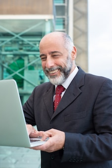 Улыбающийся зрелый человек, используя ноутбук на улице