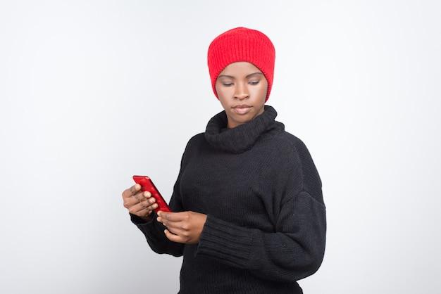 現代の携帯電話を保持している思いやりのあるアフリカ系アメリカ人女性