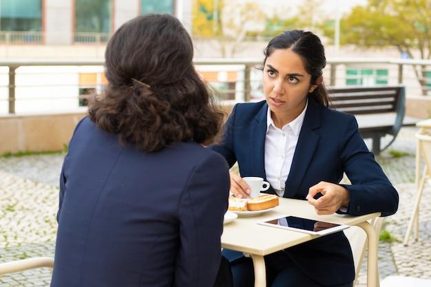 Деловая женщина пьет кофе и обсуждает работу