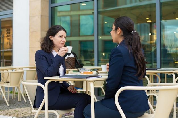 Деловая женщина пьет кофе в кафе на открытом воздухе