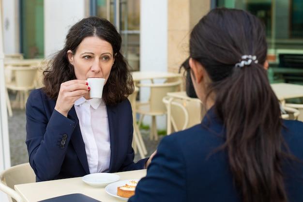 屋外カフェでコーヒーを飲むビジネス部門の同僚