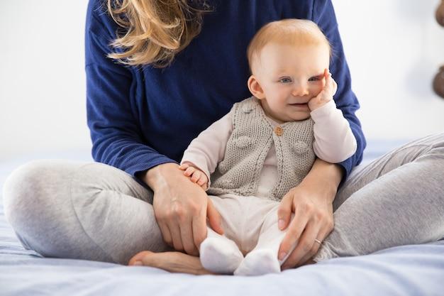 母親の腕の中で座っている陽気な赤い髪の赤ちゃん女の子