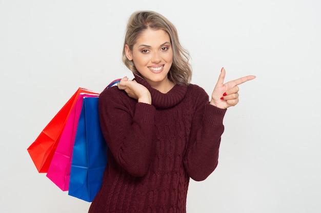 Веселая молодая женщина, держащая сумок