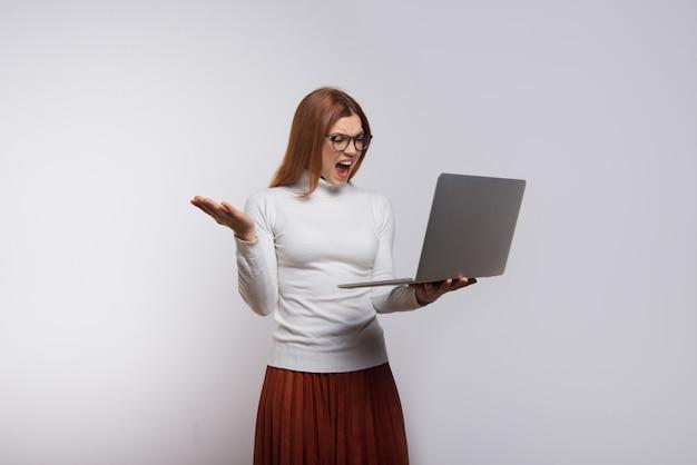 Эмоциональная женщина держит ноутбук и кричит