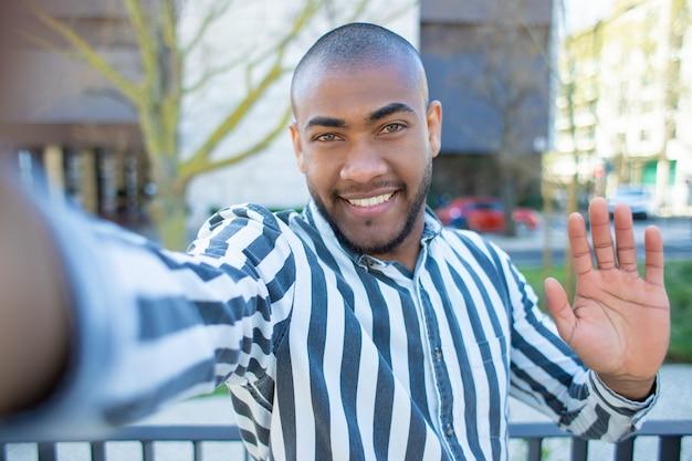 手を振っているハンサムな笑顔のアフリカ系アメリカ人の男