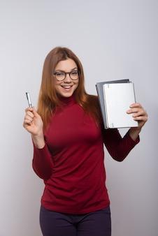 Счастливая студентка с учебниками и ручкой