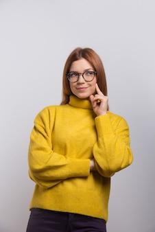 Задумчивая молодая женщина в очках смотрит вверх