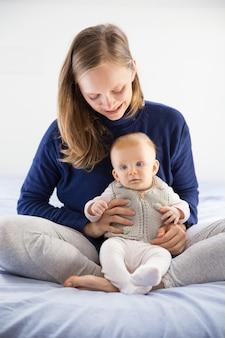 彼女のかわいい小さな赤ちゃんを保持している肯定的な若い新しいお母さん