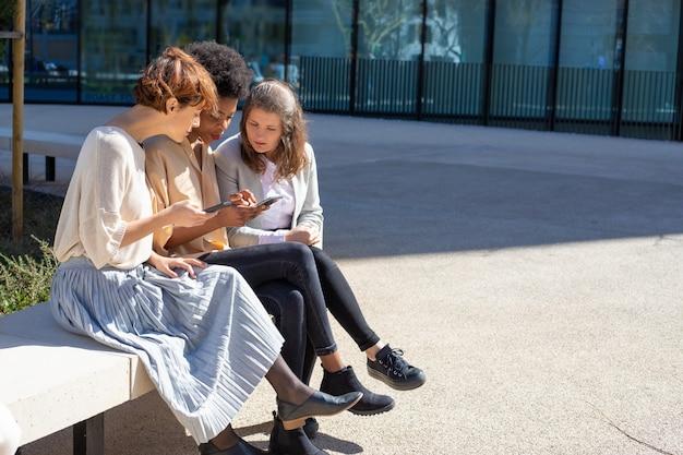 Расслабленные женщины со смартфонами разговаривают на улице