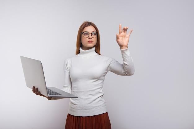 Серьезная женщина держит ноутбук и трогательно воздух рукой