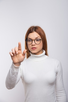 Серьезная женщина нажимает виртуальную кнопку