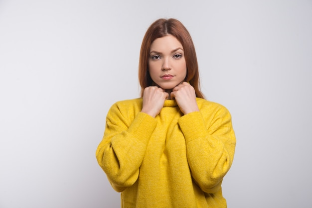 Серьезная молодая женщина в желтом свитере
