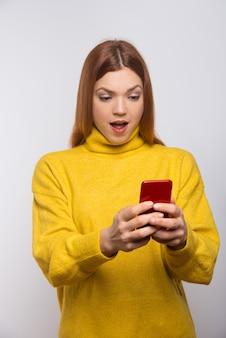 Шокирован молодая женщина с помощью смартфона