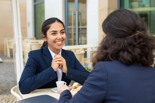 Улыбающиеся девушки разговаривают и пьют кофе