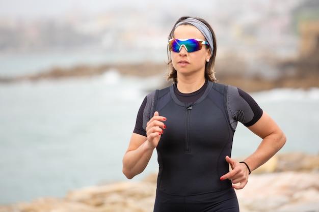海の海岸で実行されているスポーティな女性