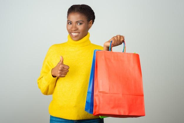 買い物袋を保持している陽気な満足している顧客