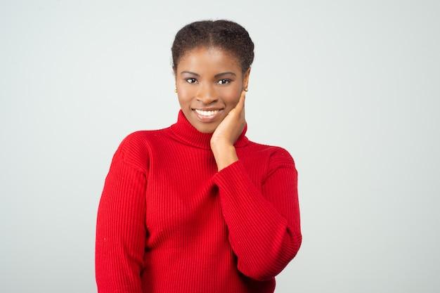 顔の皮膚に触れる肯定的な笑顔の女性