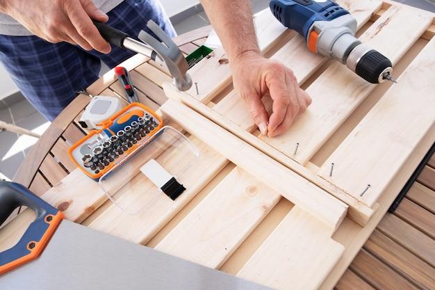 Руки вбивают гвоздь с молотка в деревянную полку