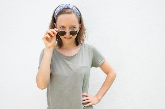 ヘアバンドと夏の服を着て陽気な若い女性