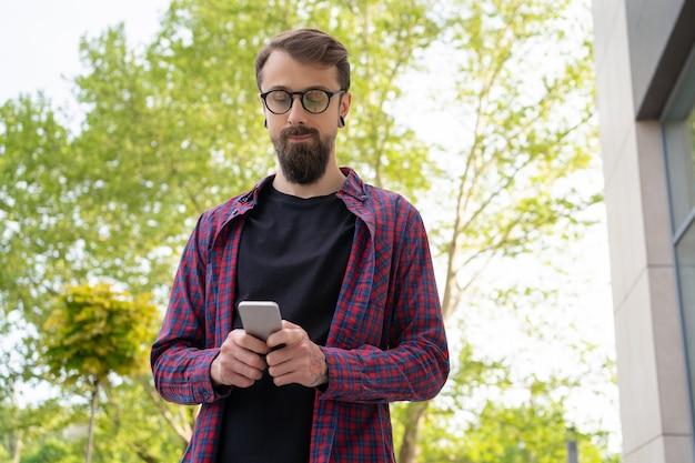 通りでスマートフォンを保持している丸い眼鏡の黒髪の男