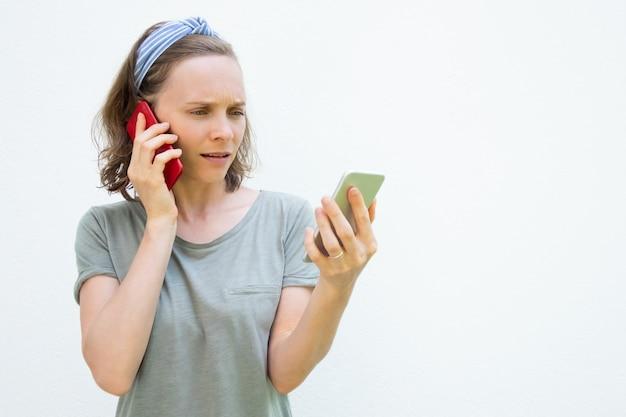 Сосредоточена занятая молодая женщина, используя два смартфона