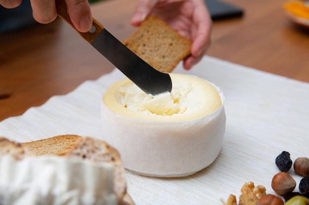 Рука берет мягкий сыр с ножом, чтобы намазать на хлеб