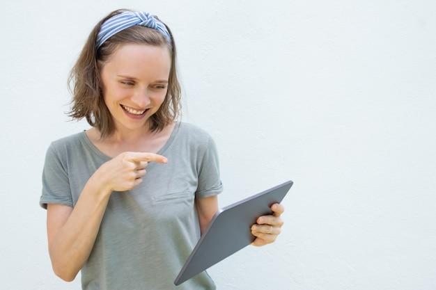 ビデオトークにタブレットを使用して幸せな陽気な若い女性
