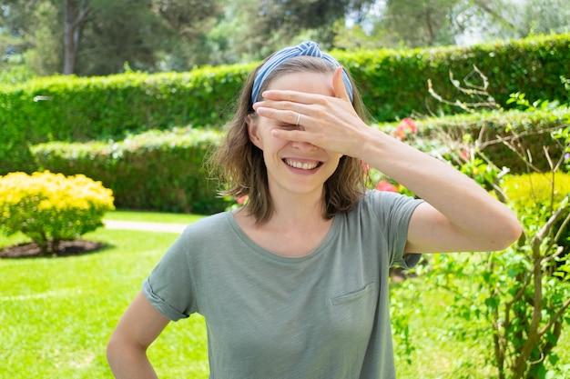 太陽から目を覆っている夏の服装で幸せな女