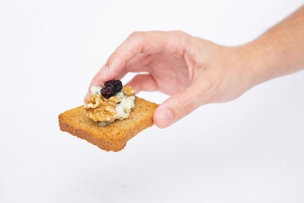 Человеческая рука держит поджаренный ломтик хлеба с голубым сыром