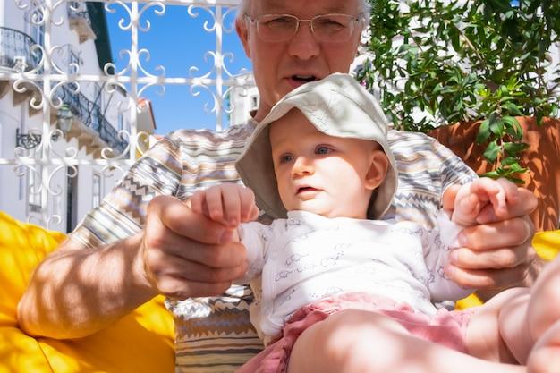 Зрелый мужчина держит внучку очаровательны младенца