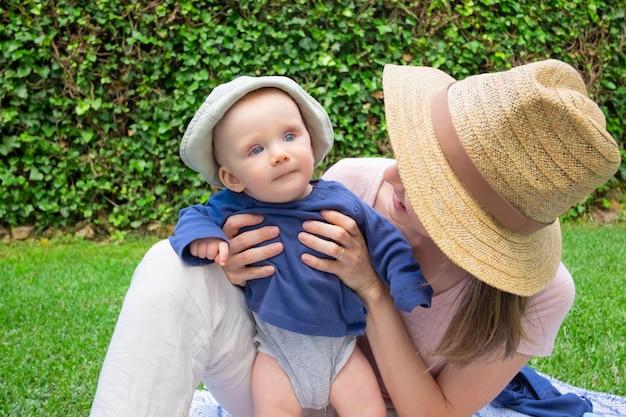 Молодая мама в шляпе держит дочь, глядя на нее