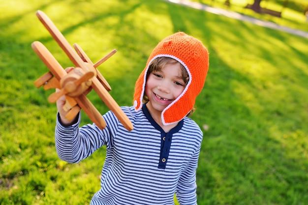 オレンジ色のヘルメットパイロットの草の背景に対しておもちゃの木製の飛行機で遊ぶ少年