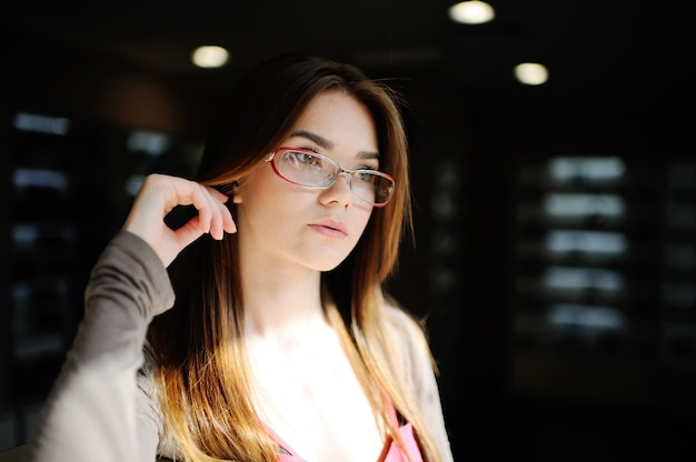 光学の店でメガネで美しい少女。悪い視力