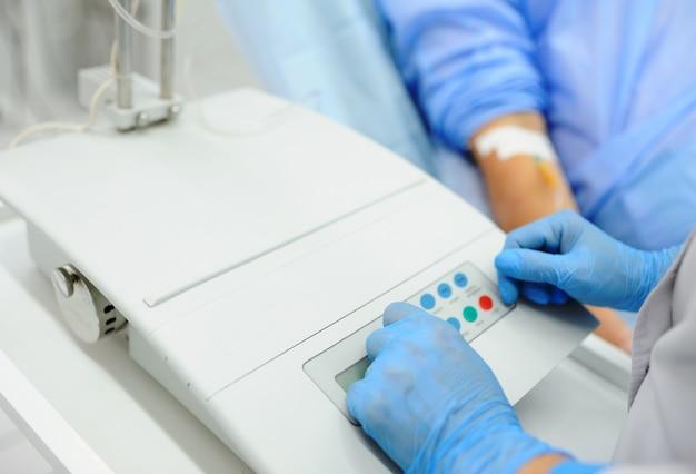 医者は静脈に点滴で患者の背景の医療機器が含まれています