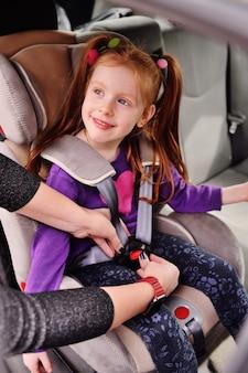 赤い髪の少女が車の中で微笑みます。