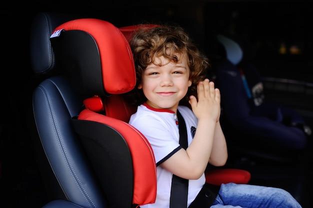 赤い子供の車の座席に座っている男の子