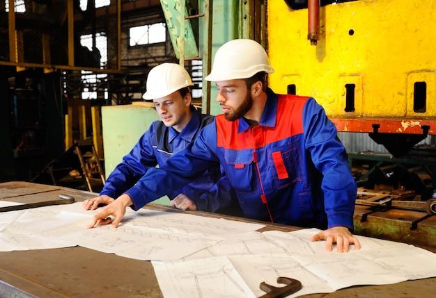 Двое рабочих в строительных касках обсуждают план, план или промышленный проект на заднем плане завода