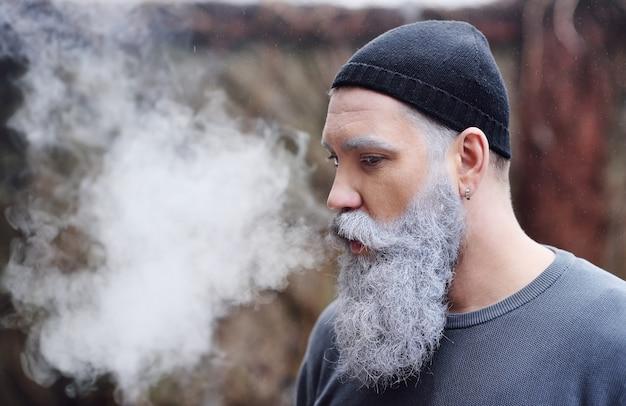 灰色のひげと口ひげをリリース魅力的なスタイリッシュな男