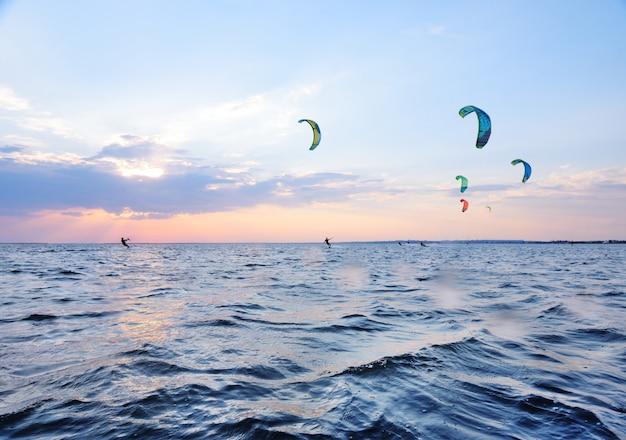 人々はカイトボードの海で泳ぐ