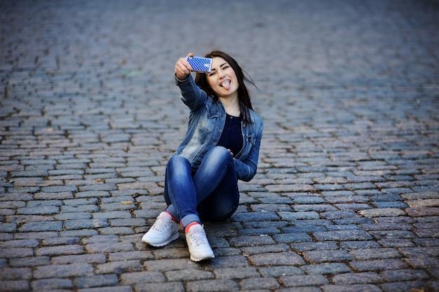 女の子は携帯電話で自分自身を撮影