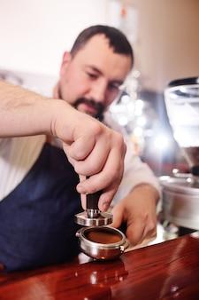 Милый бородатый мужчина бариста держит держатель с молотым кофе